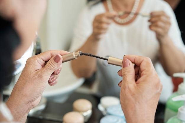 Handen van onherkenbare hogere dame die mascara voor spiegel houden Gratis Foto