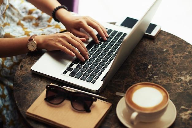 Handen van onherkenbare jonge vrouw die laptop in koffie met behulp van Gratis Foto