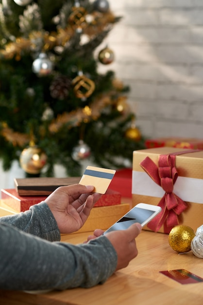Handen van onherkenbare smartphone en de creditcard van de mensenholding voor kerstboom Gratis Foto