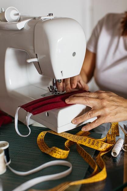 Handen van oude gezichtsmaskers van de vrouwen naaiende doek voor vrienden Gratis Foto