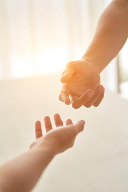 Handen van paar strekte zich uit tot elkaar tegen de zonovergoten kamer Gratis Foto