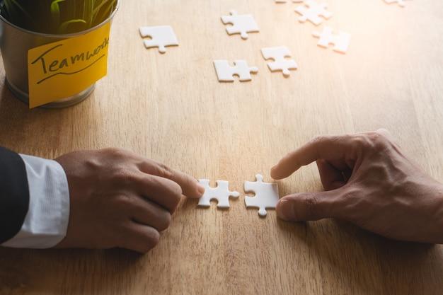 Handen van twee zakenlieden die puzzel op de werkende lijst samenvoegen. Premium Foto