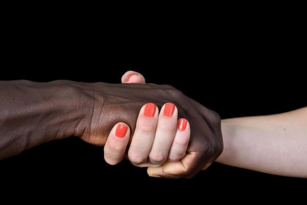 Handen van zwarte man en witte vrouw op zwarte achtergrond Premium Foto