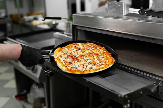 Handen zet de pizza in de oven Premium Foto