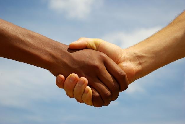 Handenhandenschudden en grijze hemel Premium Foto