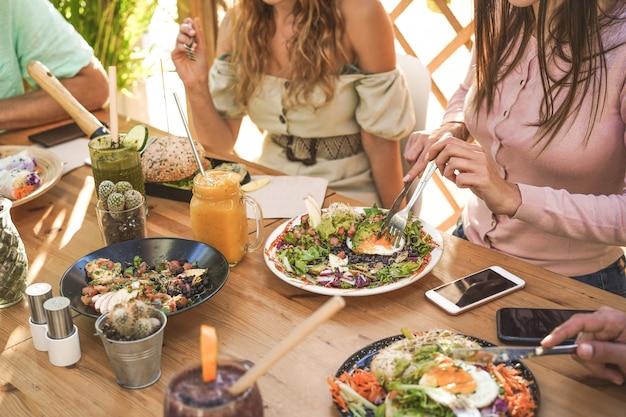 Handenmening van jongeren die brunch eten en smoothieskom met ecologische rietjes in trendy barrestaurant drinken Premium Foto
