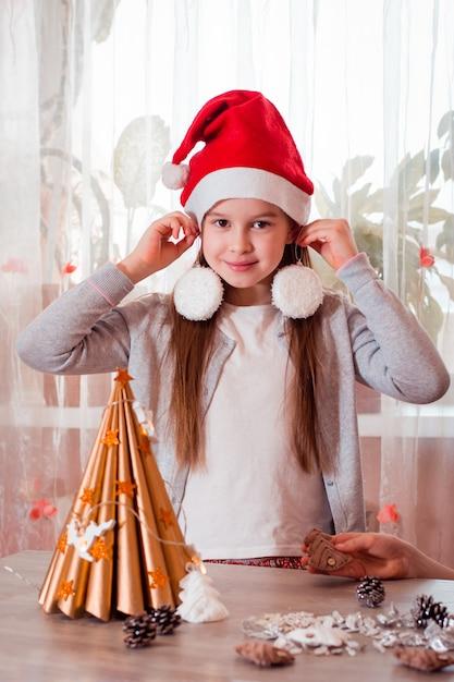 Handgemaakte kerst. het meisje probeert kerstboomversieringen als oorbellen. verticale weergave Premium Foto