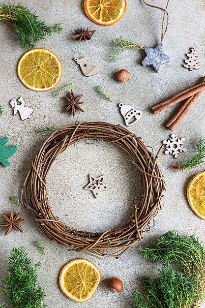 Handgemaakte kerstkrans met houten kerstspeelgoed, gedroogde stukjes sinaasappel en kruiden Premium Foto