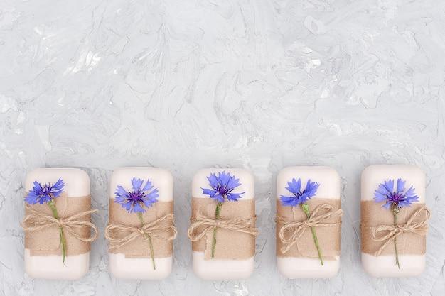 Handgemaakte natuurlijke zeepset versierd met ambachtelijk papier, gesel en blauwe bloemen. biologisch cosmetica concept. Premium Foto
