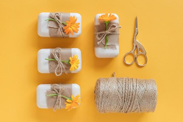 Handgemaakte natuurlijke zeepset versierd met kraftpapier, oranje calendulabloemen, streng van touw en schaar. Premium Foto
