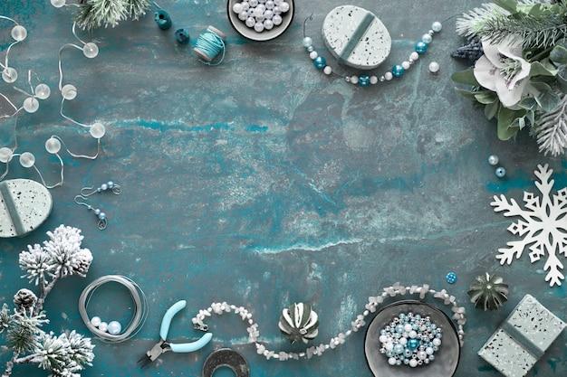 Handgemaakte sieraden maken voor vrienden als kerstcadeaus. plat lag op een donkere gestructureerde achtergrond met kopie-ruimte. Premium Foto