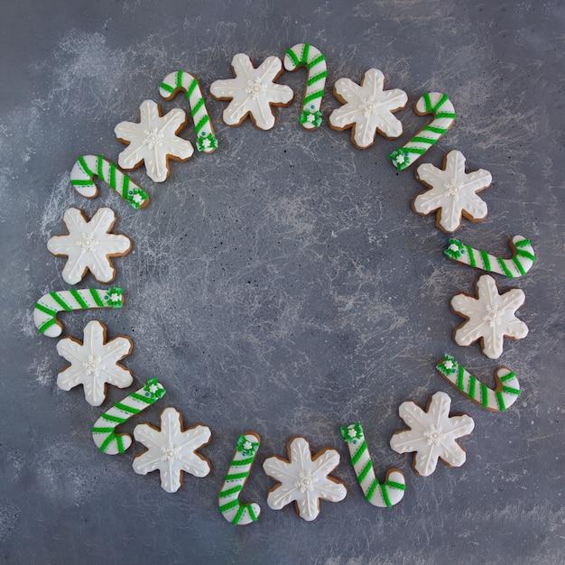 Handgeschilderd groen en wit snoepriet en sneeuwvlokken van de kerstmispeperkoek op een mooie grijze achtergrond. Premium Foto