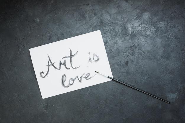 Handgeschreven 'kunst is liefde'-tekst op wit papier met penseel over leisteen oppervlak Gratis Foto