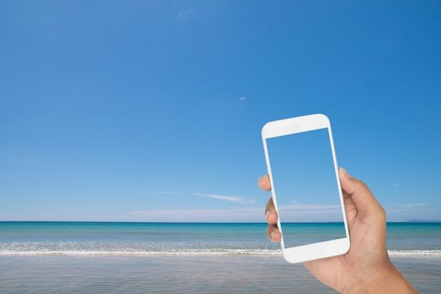 Handholding van smartphone met tropische overzees en strand als achtergrond Premium Foto