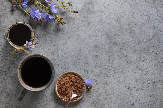 Handige cichoreidrank en blauwe bloemen. gezonde kruidendrank, koffiesurrogaat. ruimte voor tekst. uitzicht van boven. Premium Foto