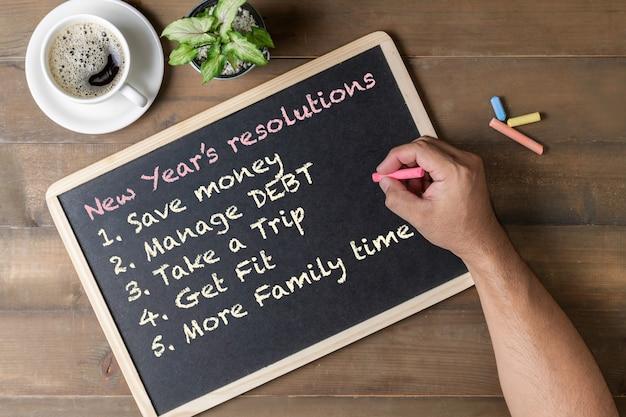 Handmens die nieuwjaarresolutie op zwarte raad schrijven Premium Foto