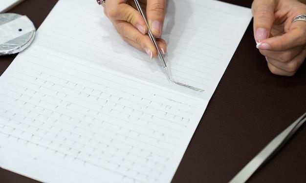 Handoefening en training wimper verlenging op papier in de klas, werken met twizzers Premium Foto