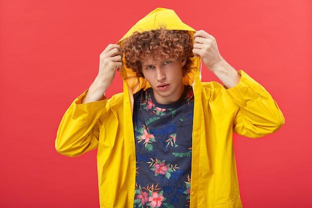 Handosme jonge hipster die de kap van zijn gele modieuze anorak aanpast voordat hij uitgaat Gratis Foto