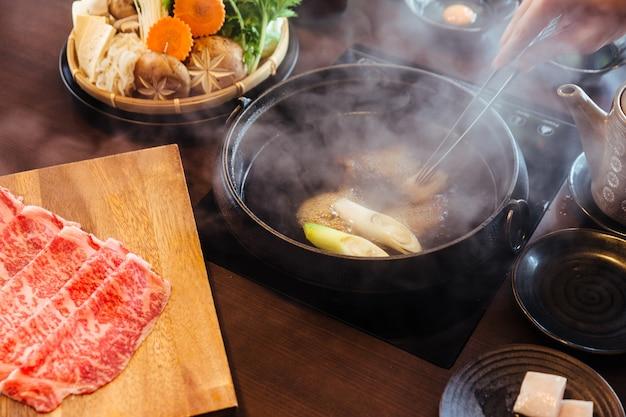 Handroerende warme en kokende shabu-bouillon met a5 wagyu en kurobuta-varkensvlees. Premium Foto