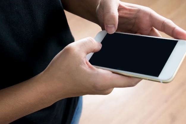 Hands-on mensen met zwarte t-shirts gebruiken technologie om iets in de telefoon te vinden. Premium Foto