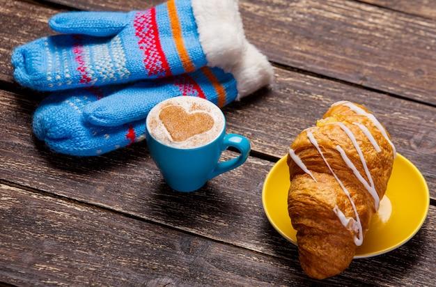 Handschoenen en een kopje koffie op houten tafel. Premium Foto