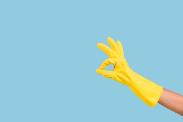 Handschoenenhand met ok gebaarteken tegen blauwe achtergrond Gratis Foto
