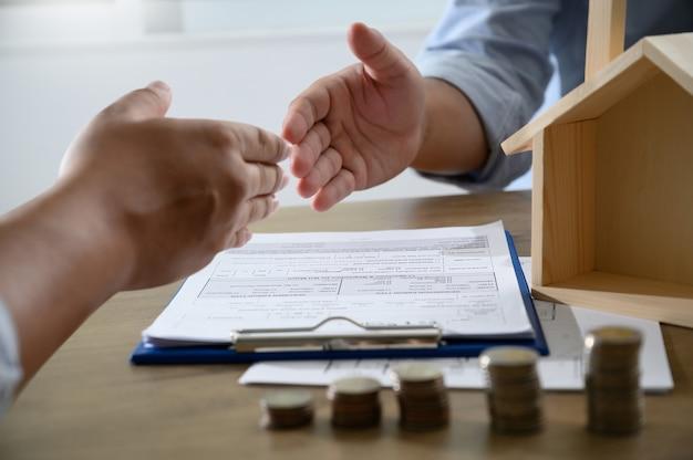Handshaking kaukasische makelaar onroerend goed en overeenkomst Premium Foto