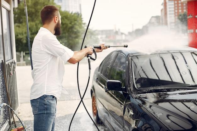 Handsomenmens in een wit overhemd die zijn auto wassen Gratis Foto