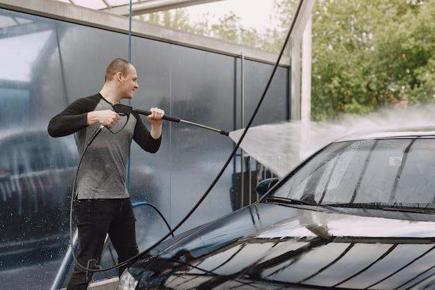 Handsomenmens in een zwarte sweater die zijn auto wassen Gratis Foto