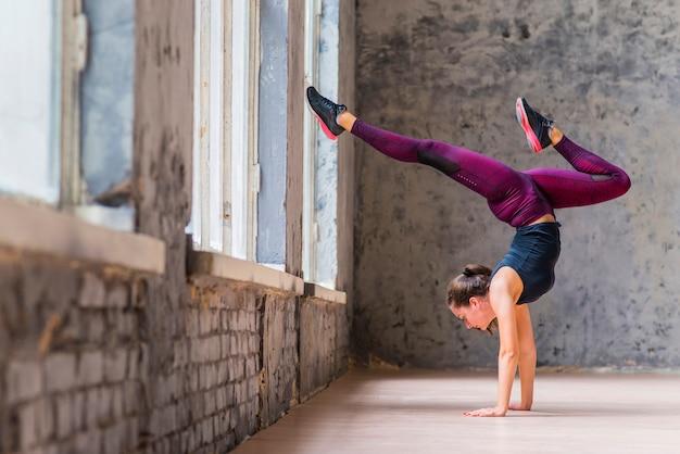 Handstand yogi vrouw beoefenen van yoga naar beneden gerichte boom vormen Gratis Foto