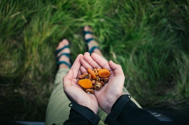 Handvol gezonde noten, rozijnen en gedroogd fruit buiten in de wildernis. snelle snack tijdens wandeling in de bergen. Gratis Foto