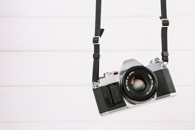 Hangende camera voor witte achtergrond Gratis Foto