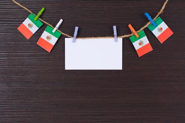 Hangende vlaggen van mexico in bijlage aan kabel met wasknijpers met copyspace op wit notadocument Premium Foto