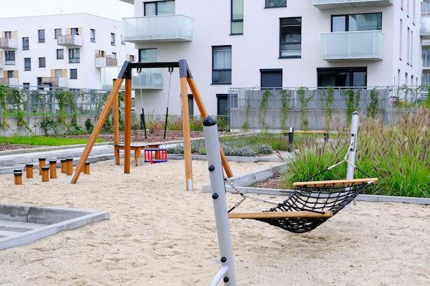 Hangmat en schommel op een kinderspeelplaats in de gezellige binnenplaats van de moderne woonwijk. Premium Foto