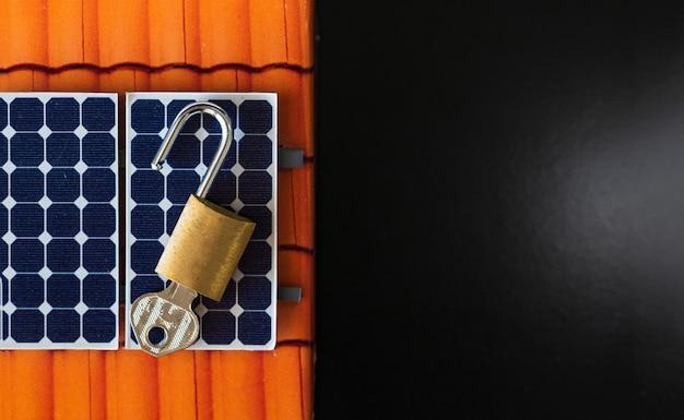 Hangslot met sleutel op fotovoltaïsch zonnepaneel op zwart Premium Foto
