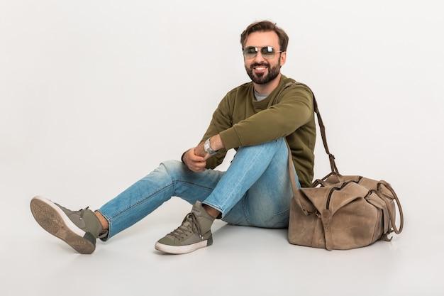 Hansome bebaarde stijlvolle man zittend op de vloer geïsoleerd gekleed in sweatshirt met reistas, spijkerbroek en zonnebril dragen Gratis Foto