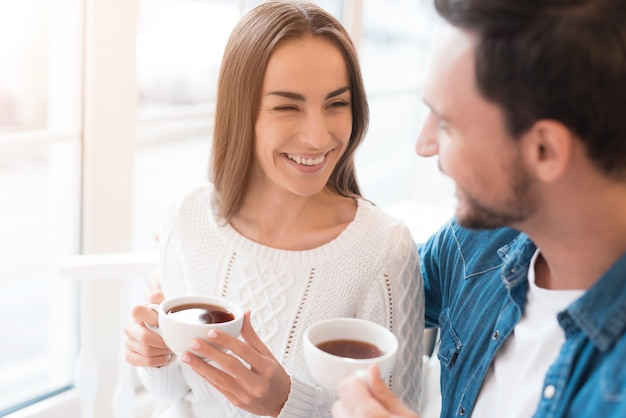 Happy couple in love drinks tea at home of cafe. Premium Foto