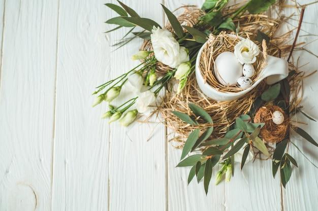 Happy easter achtergrond. paaseieren in een kop op een houten witte achtergrond met bloemendecoratie. vrolijk pasen concept Gratis Foto