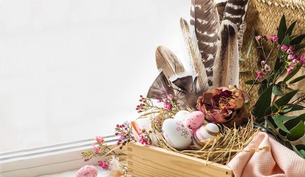 Happy easter achtergrond. roze paaseieren in een nest met florale decoraties en veren in de buurt van het venster Gratis Foto