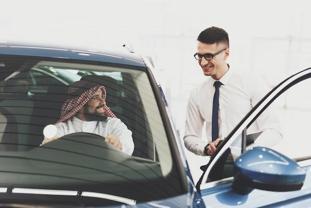 Happy kuwaiti man and car dealer in showroom. Premium Foto
