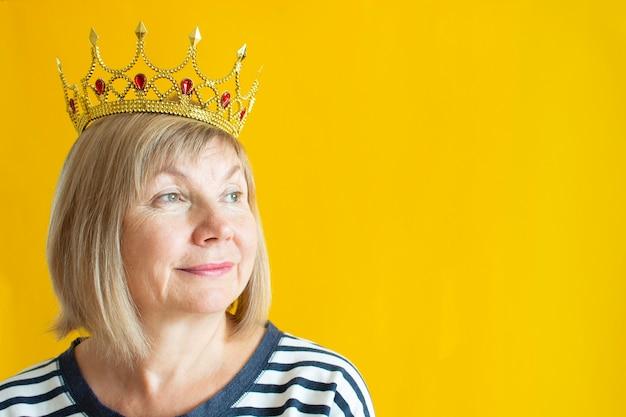 Happy lachende senior vrouw op gele achtergrond met een schattige kroon op haar hoofd. het concept van ouderdom in vreugde, over anciënniteit, schattige grootmoeder, pensioen. anti veroudering Premium Foto