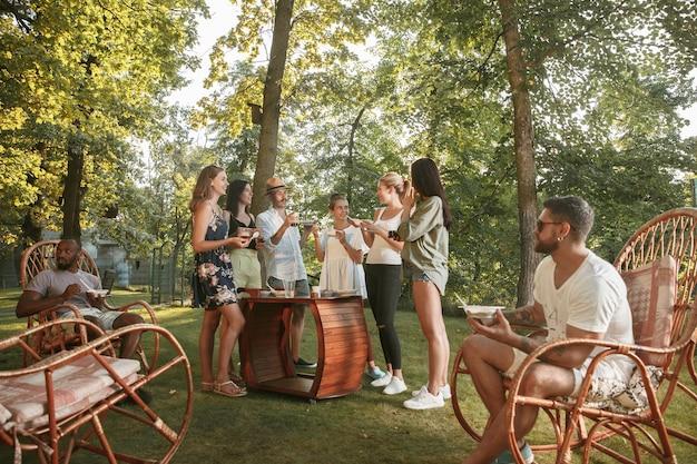 Happy vrienden eten en drinken van bier bij barbecue diner op zonsondergang tijd Gratis Foto
