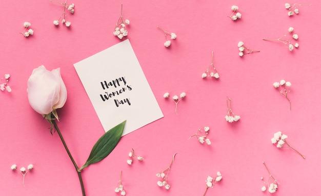 Happy womens day inscriptie op papier met roze bloem Gratis Foto