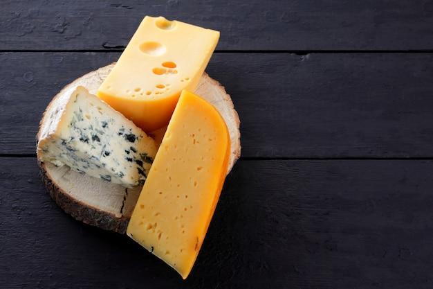 Harde kaas en blauwe kaas op houten standaard. verschillende soorten kaas op zwarte planken. Premium Foto