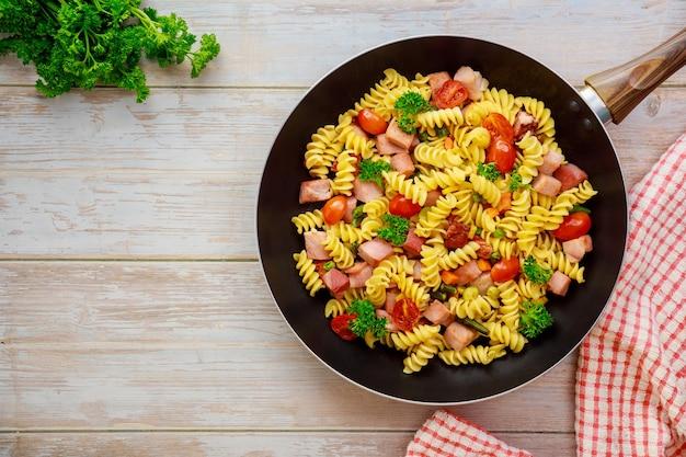 Harde tarwe griesmeel pasta met tomaat, groene erwten in de pan. bovenaanzicht. Premium Foto