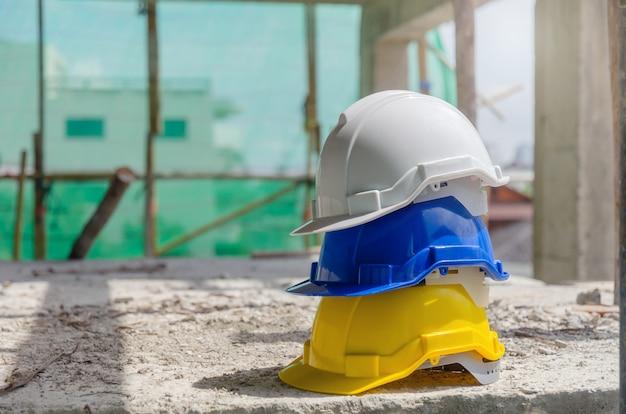 Harde veiligheidshelm voor ongevallenstapel op de vloer op de werkplek in de bouwplaats Premium Foto