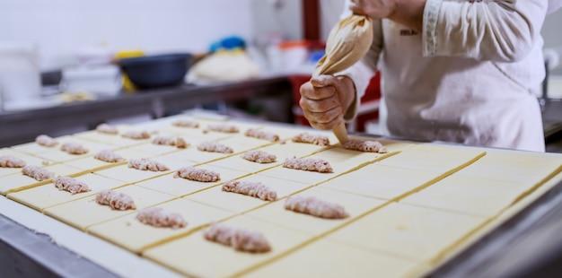 Hardwerkende bakker die gebak vult met heerlijke vla. bakkerij interieur. Premium Foto