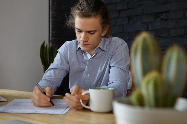 Hardwerkende geconcentreerde jonge zakenman in blauw shirt doet papierwerk in zijn kantoor, met koffie in de ochtend. mensen, baan, beroep, beroep, bedrijf en carrièreconcept. selectieve aandacht Gratis Foto