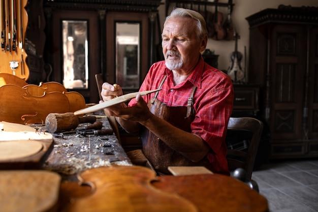 Hardwerkende senior timmerman bezig met zijn creatieve project in timmerwerkplaats Gratis Foto