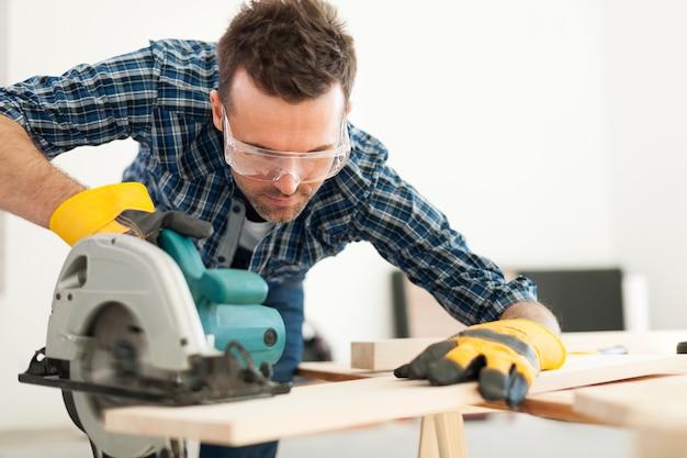 Hardwerkende timmerman die houten plank snijdt Gratis Foto